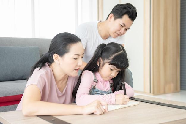 Conceito de educação. retrato feliz sorrindo amor pai e mãe de família asiática com menina asiática aprendendo
