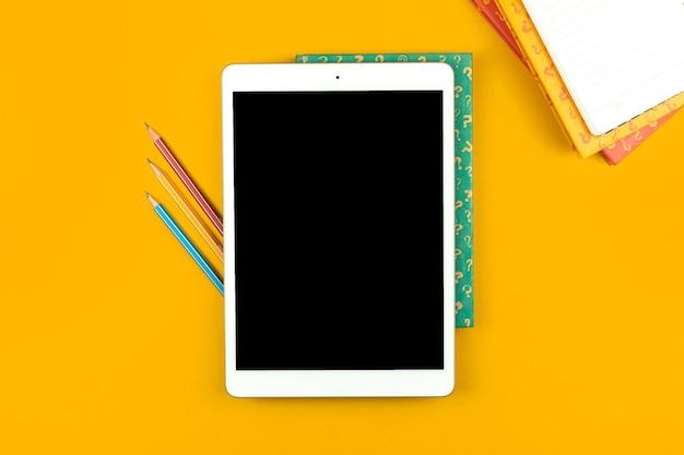 Conceito de educação, tablet de alunos com lápis na área de trabalho amarela, livros com sinais de interrogação, imagem plana e foto de vista superior