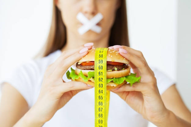 Conceito de emagrecimento, jovem mulher com a boca selada desistindo de junk food.