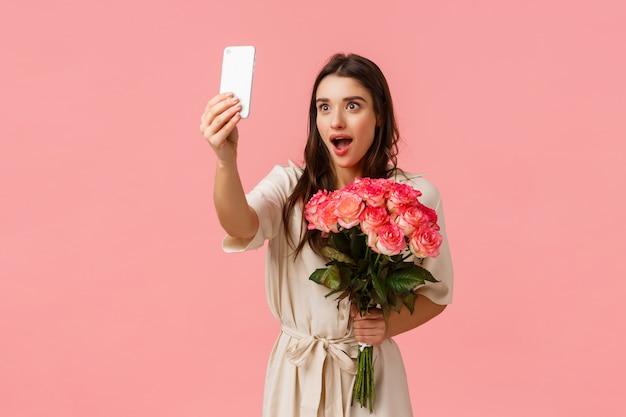 Conceito de emoções, beleza e romance. mulher morena atraente, excitada e sedutora, segurando lindas rosas, recebeu flores e tomou selfie com expressão de surpresa surpreendida, rosa