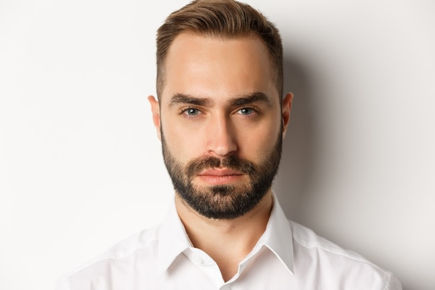 Conceito de emoções e pessoas. foto de um homem bonito de aparência séria com barba, parecendo confiante e determinado