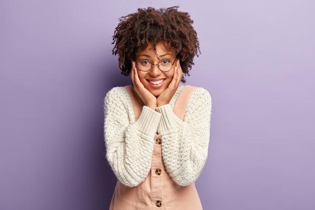 Conceito de emoções felizes. mulher jovem com penteado afro, mantém as palmas das mãos nas bochechas, em alto astral, satisfeita em ver o bebezinho, quer brincar de criança usa macacão de malha branca e macacão