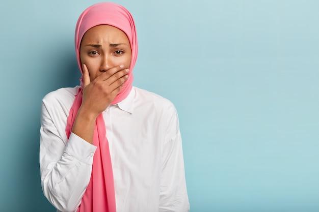 Conceito de emoções humanas negativas. mulher mestiça deprimida e deprimida em um hijab chora com más notícias, cobre a boca com a palma da mão, reclama de alguma coisa, fica dentro de casa com espaço em branco à parte