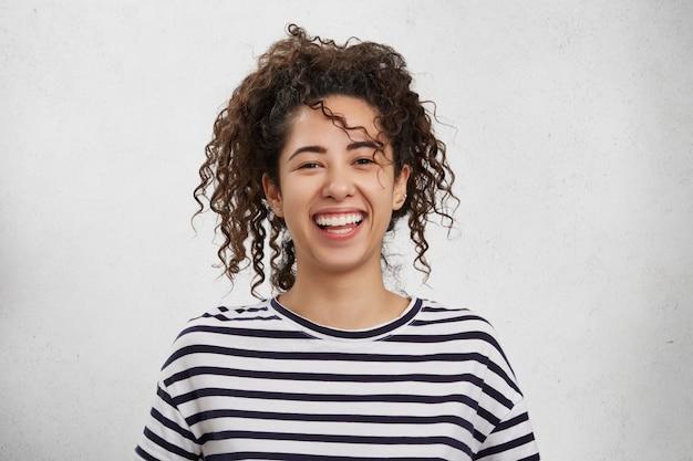 Conceito de emoções positivas. mulher jovem e emocionalmente feliz com cabelo crespo e aparência atraente