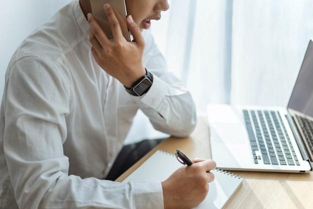 Conceito de empreendedor: um jovem empresário conversando sobre uma consultoria de telefone inteligente sobre um tema de negócios.