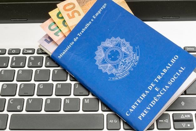 Conceito de emprego e controle financeiro com notas de dinheiro brasileiras e carteira de trabalho brasileira
