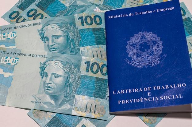 Conceito de emprego e controle financeiro com notas de dinheiro brasileiras e carteira de trabalho.