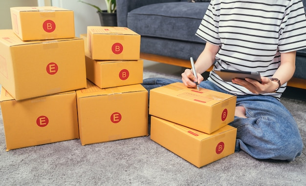 Conceito de empresa de pequeno porte de inicialização, jovem proprietário trabalhando e embalagem na caixa para o cliente no sofá no escritório em casa, vendedor prepara a entrega.