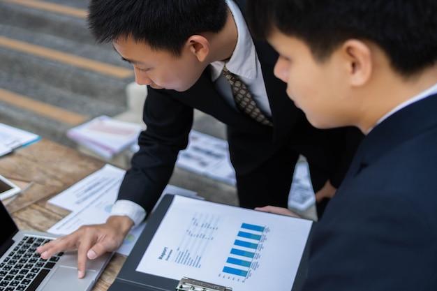 Conceito de empresário dois empresários vestindo ternos oficiais, desfrutando de participar e resolvendo problemas no plano do projeto.