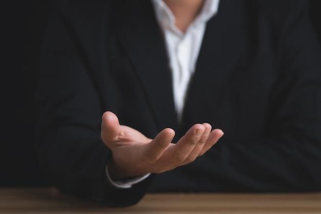 Conceito de empresário. homem de negócios sentado com as mãos abertas sobre fundo preto.
