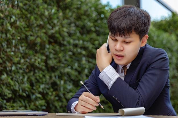 Conceito de empresário o jovem empresário falando ao telefone, uma mão segurando o smartphone enquanto a outra segurando o lápis, observando as informações do cliente.