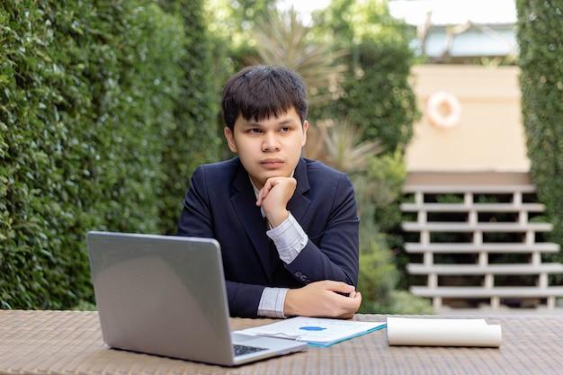 Conceito de empresário um jovem empresário em terno marinho, sentado no jardim com os documentos e o laptop na mesa parecendo pensativo e sério.