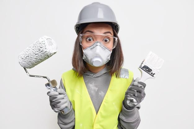 Conceito de engenharia e construção da indústria. surpresa, engenheira profissional feminina usa capacete de proteção, máscara de óculos e luvas usa escova de rolo de pintura para redecorar