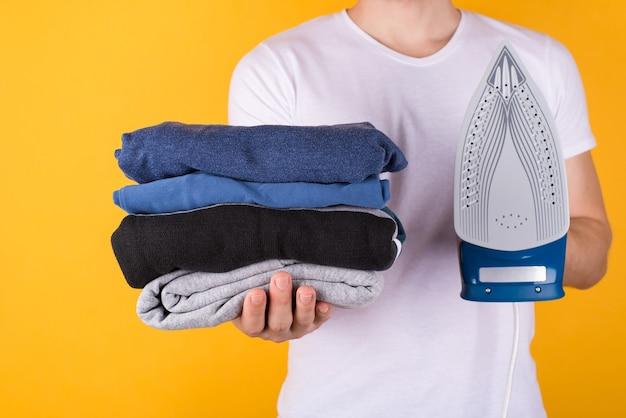 Conceito de engomadoria de roupas. foto recortada de um homem segurando uma pilha de roupas dobradas e um ferro isolado em um fundo amarelo