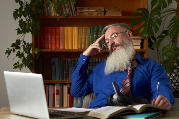 Conceito de ensino a distância. o professor olha atentamente para a tela do laptop e ouve o aluno na aula on-line, foco seletivo