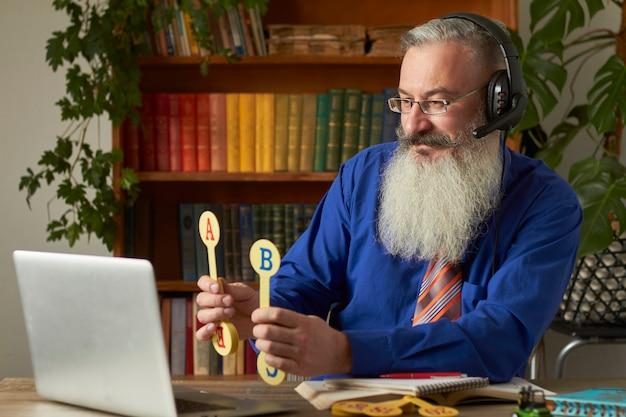 Conceito de ensino a distância para crianças pequenas. um professor tutor ensina a criança a ler e contar on-line usando o laptop.
