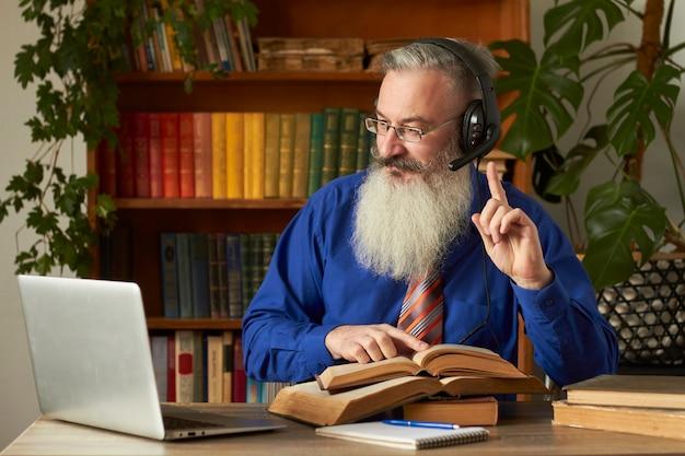 Conceito de ensino a distância. professor professor tutor em fones de ouvido ensina disciplina online. homem barbudo maduro responde a pergunta do professor através do laptop.