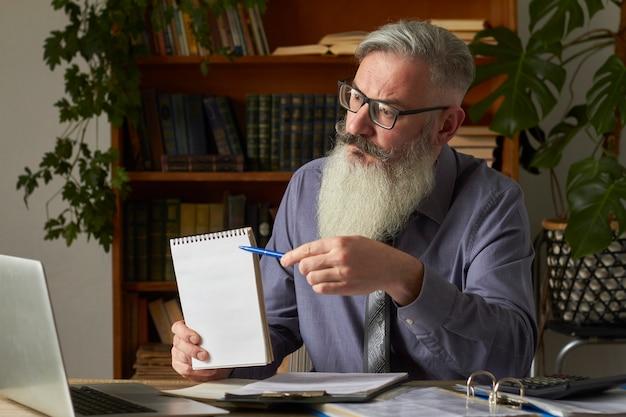 Conceito de ensino a distância. professor, tradutor, tutor na área de trabalho na biblioteca aponta com caneta no prato em branco