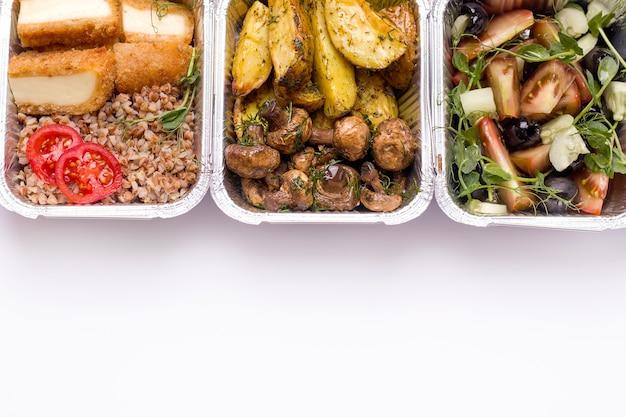 Conceito de entrega de alimentos. batatas fritas com cogumelos, salada e trigo sarraceno em um close-up do recipiente.