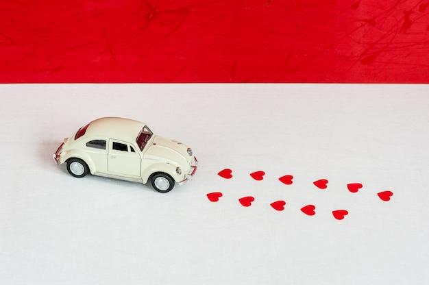 Conceito de entrega de amor. carro retrô de brinquedo e vestígios da máquina em formas de corações
