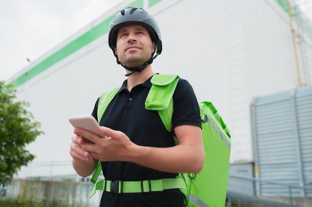 Conceito de entrega de comida. o entregador de comida usa um smartphone para alcançar os clientes mais rapidamente. courier tem uma geladeira em uma mochila verde.