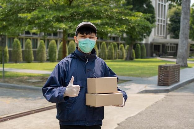 Conceito de entrega de encomendas - o jovem remetente levantando duas caixas de encomendas e parado no meio de uma rua estreita para procurar o prédio onde ele vai soltar esses dois pacotes.