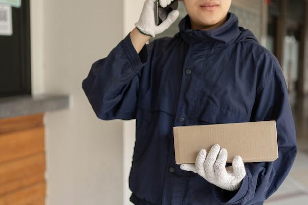 Conceito de entrega de encomendas - o transportador de correio que se posiciona em frente ao edifício e liga ao seu cliente para confirmar a morada certa para a distribuição da encomenda postal.