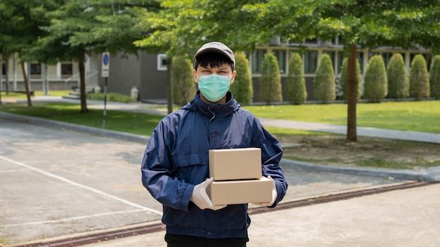 Conceito de entrega de pacotes - o jovem remetente levantando duas caixas de pacotes e parado no meio de uma rua estreita para procurar o prédio onde ele vai soltar esses dois pacotes.
