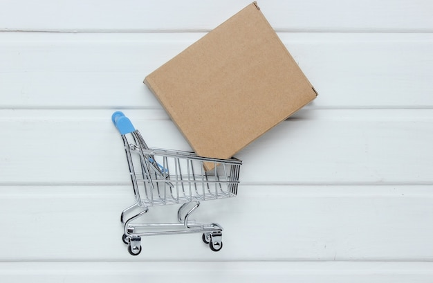 Conceito de entrega de presente. caixa de papelão e mini carrinho de compras na mesa de madeira branca.
