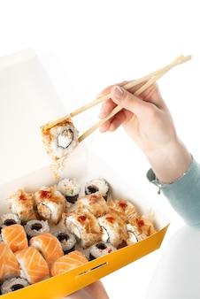 Conceito de entrega de sushi, menina segurando conjuntos de sushi em um recipiente de papel descartável, caixas de papel ecológicas