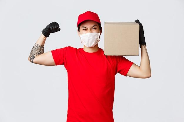 Conceito de entrega durante pandemia de coronavírus. courier mostra sua força, flexiona os bíceps e carrega um pacote pesado no ombro, usa máscara e luvas médicas para segurança na quarentena de covid-19