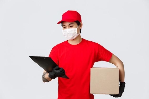 Conceito de entrega e transportadoras durante pandemia de coronavírus. correio asiático de boné vermelho uniforme, camiseta e máscara médica com luvas, segurando a área de transferência e pacote, verifique em ordem