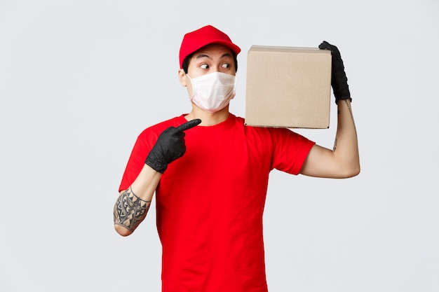 Conceito de entrega e transportadoras durante pandemia de coronavírus. entregador intrigado em uniforme, serviço de correio trazer caixa para o cliente, apontando e olhando para o pacote curiosamente, use máscara e luvas