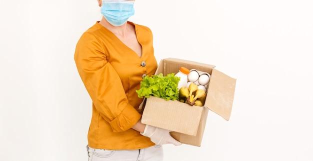 Conceito de entrega: entregador de supermercado caucasiano com caixa de compras com frutas e vegetais frescos