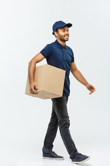Conceito de entrega - handsome african american delivery man. isolado no fundo do estúdio cinzento. espaço de cópia.
