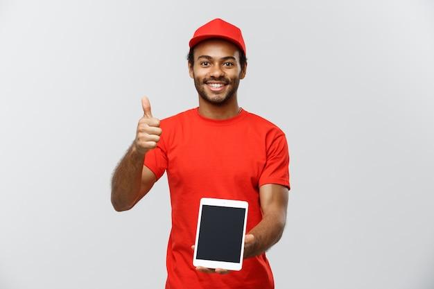 Conceito de entrega - retrato de handsome african american delivery man ou courier com caixa mostrando tablet em você para verificar a ordem. isolado no fundo do estúdio cinzento. espaço de cópia.