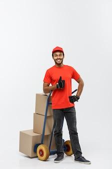 Conceito de entrega - retrato de handsome african american delivery man ou de correio empurrando caminhão manual com pilha de caixas. isolado no fundo do estúdio cinzento. espaço de cópia.