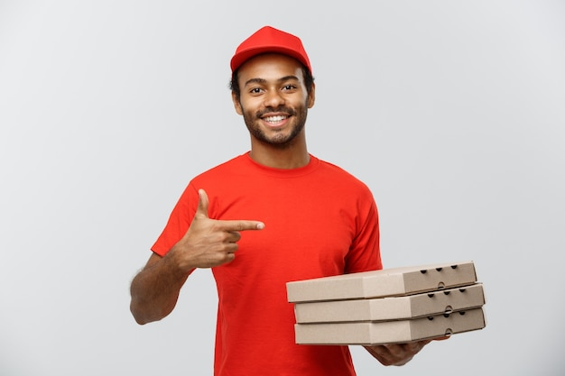 Conceito de entrega - retrato de handsome african american pizza delivery man. isolado no fundo do estúdio cinzento. espaço de cópia.