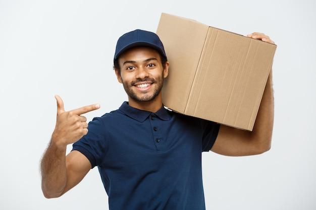 Conceito de entrega - retrato de um homem de entrega feliz americano africano apontando mão para apresentar um pacote de caixa. isolado no fundo do estúdio cinzento. espaço de cópia.