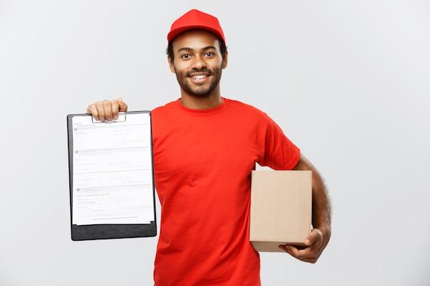 Conceito de entrega - retrato do homem de entrega afro-americano bonito ou de um mensageiro que mostra um formulário de documento de confirmação para assinar. isolado no fundo do estúdio cinzento. espaço de cópia.