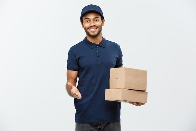 Conceito de entrega - retrato do homem de entrega feliz africano-americano em pano vermelho, segurando um pacote de caixa. isolado no fundo do estúdio cinzento. espaço de cópia.