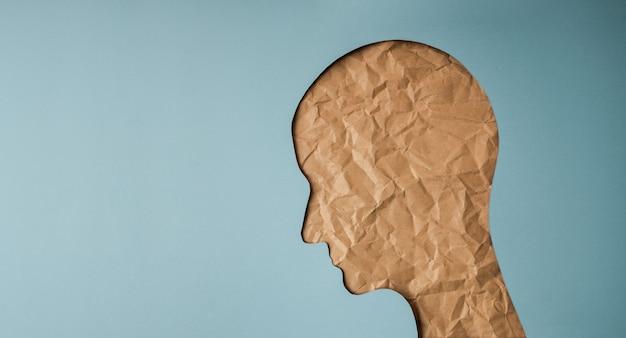 Conceito de envelhecimento. forma de cabeça de mulher criada por corte de papel artesanal amassado. senhora velha de pele enrugada. rosto feminino de tristeza