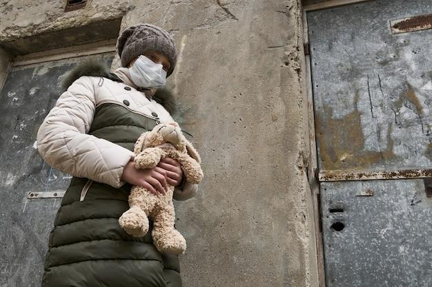 Conceito de epidemia e quarentena - uma menina com uma máscara facial e