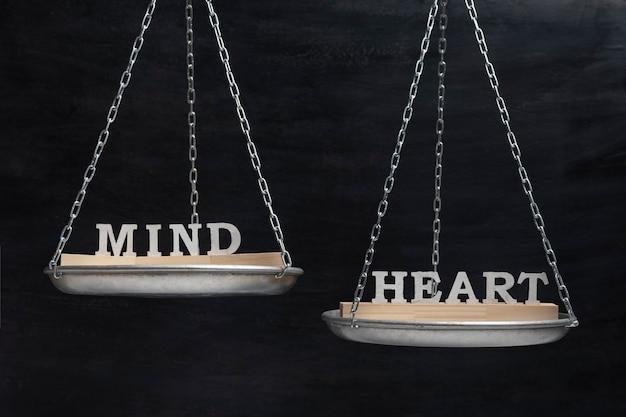 Conceito de equilíbrio de mente e coração. escalas em fundo preto close-up.