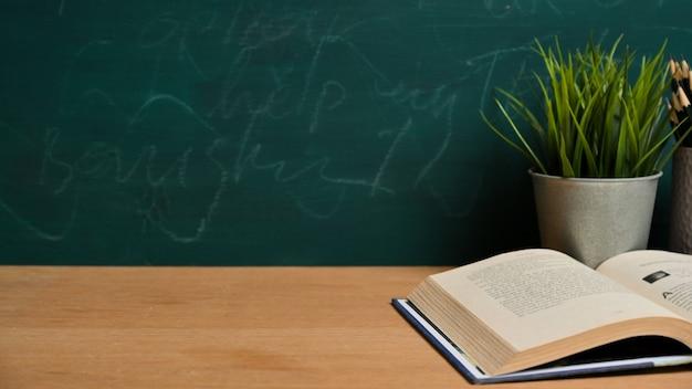 Conceito de escola e conhecimento, espaço vazio de maquete para exposição de produtos na mesa de madeira com o livro aberto sobre a lousa verde