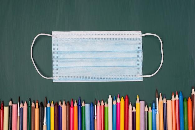Conceito de escolaridade remota. conceito de bloqueio. foto de visão superior acima da máscara e lápis coloridos isolados no quadro verde