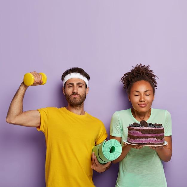 Conceito de escolha certa. homem forte e musculoso em camiseta amarela, levanta a mão com halteres, sendo um estilo de vida saudável