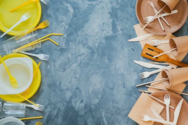 Conceito de escolha de louças sustentável vs plástico. foto da vista superior acima de utensílios de plástico e madeira brancos e amarelos em comparação com um fundo cinza. Foto Premium