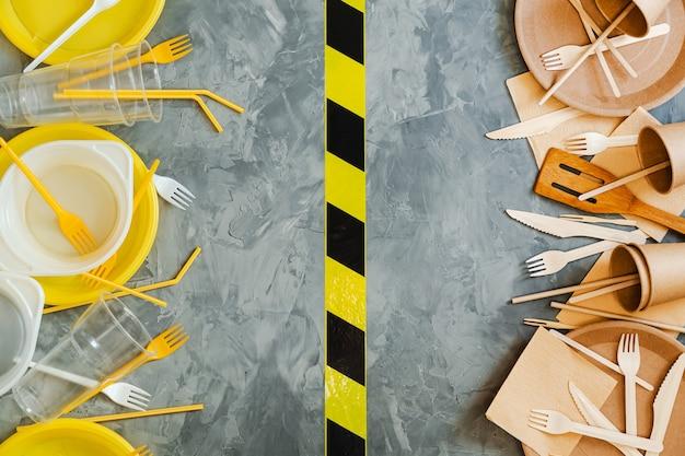 Conceito de escolha de louças sustentável vs plástico. foto da vista superior acima de utensílios de plástico e madeira brancos e amarelos em comparação com um fundo cinza.