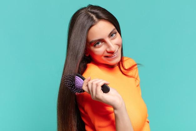 Conceito de escova de cabelo de expressão jovem e bonita adolescente feliz e surpresa